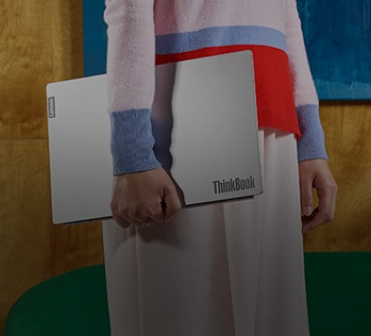 Woman holding a ThinkBook laptop